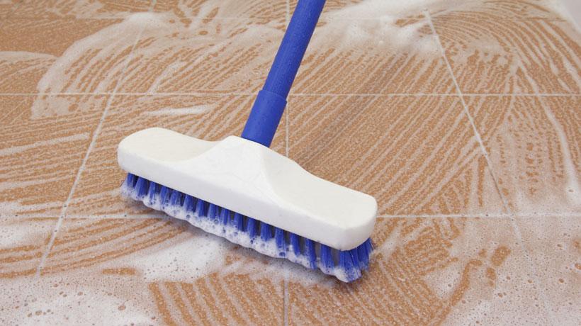esfregando o piso com vassoura e  produto antiderrapante